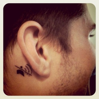 Photo of a man with a mute symbol tattooed behind his ear