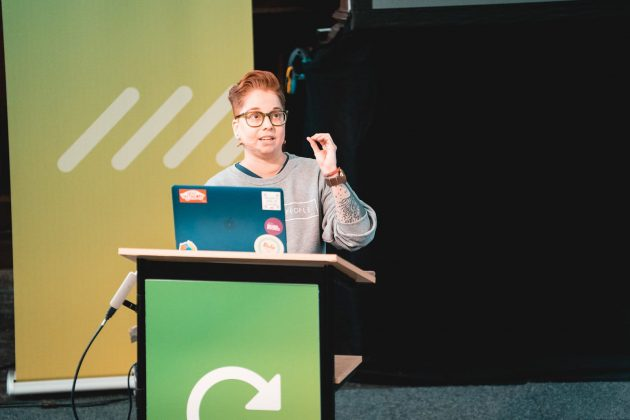 Darice standing behind her macbook giving a talk